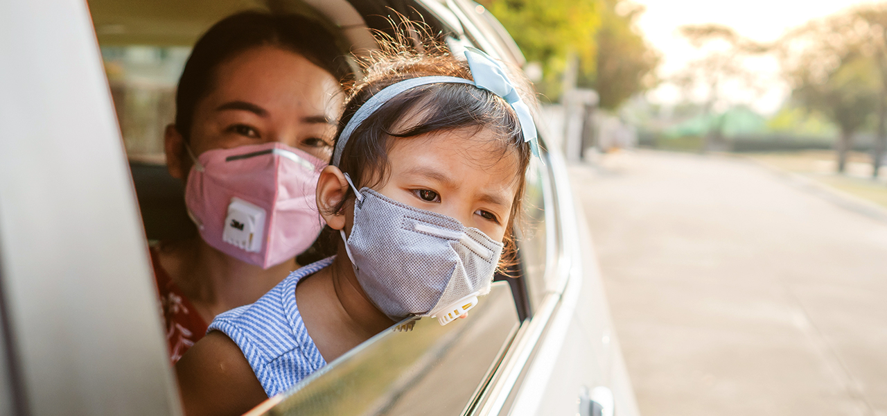 A woman in a car wearing a mask and holding a young child also wearing a mask